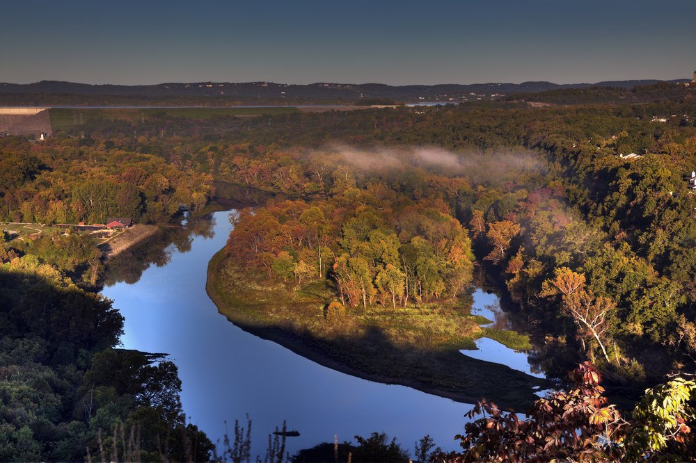 Scenic overlook at sunrise in Branson, Missouri showing the water reservoir from the Table Rock Lake Dam and colorful fall foliage.