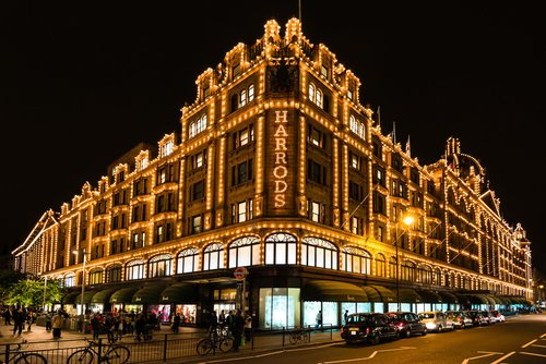 The famous Harrods department store in the evening at Knightsbridge in London, UK. Harrods is the biggest department store in Europe and offers over one million square feet of retail space, acting as a magnet for rich clients and numerous tourists throughout the year.